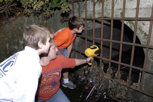 Linda McGinesss, water technician intern from Oak Ridge Institute of Science and Education, shines a light into the largest residential storm water outfall on post to show North Fort Lewis Youth Center volunteers an example of the kind of water pollution they hope to prevent.