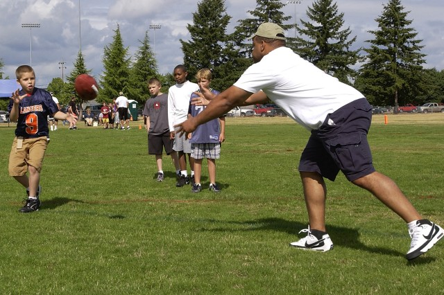 Donald Jones tosses the strong side pitch after teaching the children the proper footwork Saturday.