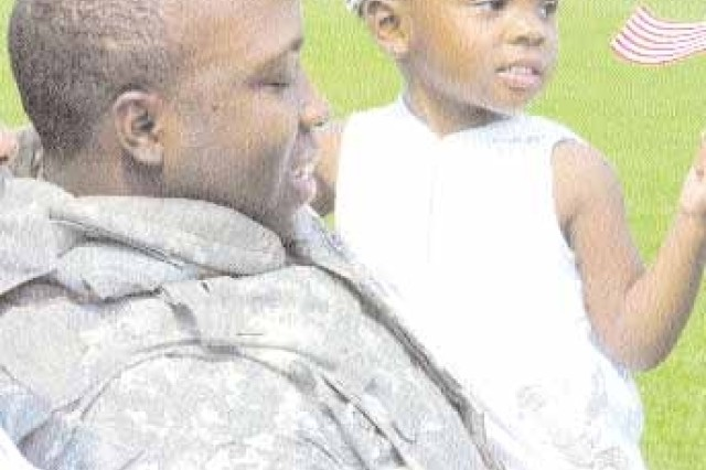 Staff Sgt. Seddrick Crusoe, HHC, 3rd Sustainment Brigade holds his child Caury Crusoe, 2, after being reunited with his Family following his 15-month deployment to Iraq, Aug. 7.