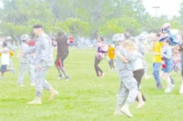 Families rush to meet returning Soldiers from the 3rd Sustainment Bde., Aug. 7  on Cottrell Field.