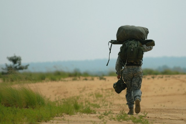 FORT BRAGG, NC - A lone Soldier from the U.S. Army Civil Affairs and Psychological Operations Command(Airborne) walks back to the rally point after making a successful combat equipment jump from a C-41A CASA airplane onto Sicily Drop Zone here on 27 July.  USACAPOC (A) Soldiers continually conduct sustain airborne training to maintain their jump proficiency in airborne operations.
