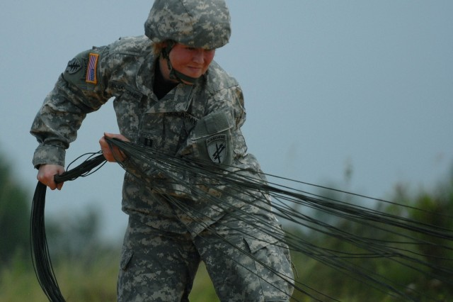 FORT BRAGG, NC - U.S. Army Reserve Capt. Amanda G. Dodd-Conner collects her parachute lines to store her chute after making a successful jump from a C-41A CASA airplane onto Sicily Drop Zone here on 27 July. She was one of five jumpmasters responsible for sustain airborne training within the U.S. Army Civil Affairs and Psychological Command (Airborne).