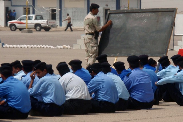 A senior IP teaches new recruits on the parade training grounds at the IP Station in Amarah.
