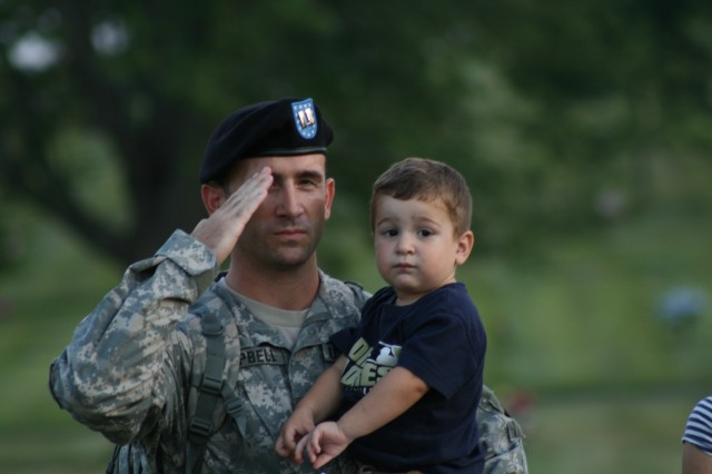 Capt. Tomas Campbell salutes the colors with his son during the All Veterans Healing Field at Davenport, Iowa's Opening Ceremony August 14.