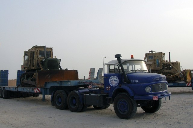 Two recently-arrived Caterpillar D7 Bulldozers await movement into the 1st Battalion, 401st Army Field Support Brigade maintenance area at Camp As Sayliyah, Qatar, August 7, 2008. The battle-weary earthmovers await service and repair, and will eventually get back in the fray.