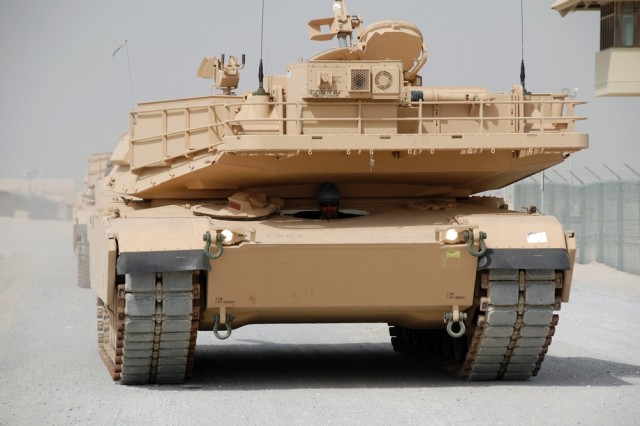 The rear of an M1 Abrams tank turret creates some welcome shade for the driver, a contract employee at Camp Arifjan, Kuwait, Aug. 6, 2008.  The shade helped combat the effects of the 113 degree temperature on this date - which was a bit on the cool side, by mid-summer standards in Kuwait.