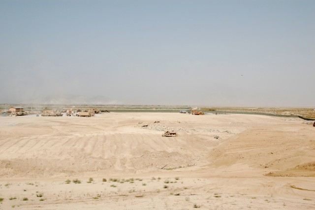 "The view from a bucket lift, 30 feet above ground, of the work underway on the Eastern expansion of the 401st Army Field Support Brigade area at Bagram Airfield, Afghanistan, Aug. 13, 2008.  The smaller concrete slab in the middle left of the photo is the future site of the Army Oil Analysis Program facility, while the work visible in the top right is for the site of the Counter Radio-Controlled Improvised Explosive Device Electronic Warfare or ""CREW"" Facility.  In addition to the AOAP and CREW sites, additional billeting for Army Materiel Command Soldiers and civilian employees is planned."