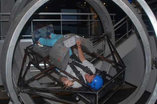 Mallory Harder, U.S. Army Garrison Wiesbaden, Germany, rides the Multi-Axis Trainer at the Euro Space Center in Transinne, Belgium. Harder participated in an Installation Management Command-Europe space camp, which is part of its Camp A.R.M.Y. Challenge program for children of deployed servicemembers.