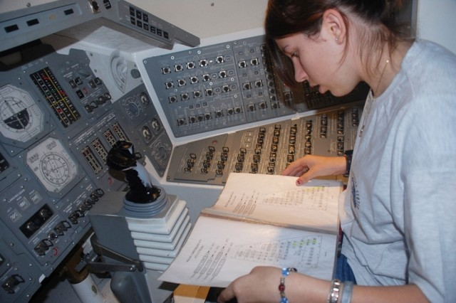 Chelsea Ryan, U.S. Army Garrison Wiesbaden, Germany, reviews a checklist in preparation for a simulated space shuttle launch at the Euro Space Center in Transinne, Belgium. Ryan was one of 24 participants in a space camp hosted by Installation Management Command-Europe as part of its Camp A.R.M.Y. Challenge.