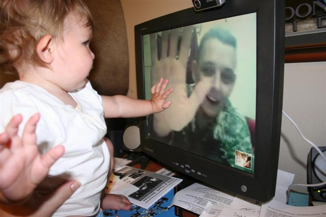 A Soldier with the 4th Brigade Combat Team, 10th Mountain Division (Light), Multi-National Division – Baghdad, shares a high-five with his daughter during a web camera communication. The Soldier was high-fiving his daughter from a forward operating base in Iraq where he is located and she was returning it from several thousand miles away in the U.S.