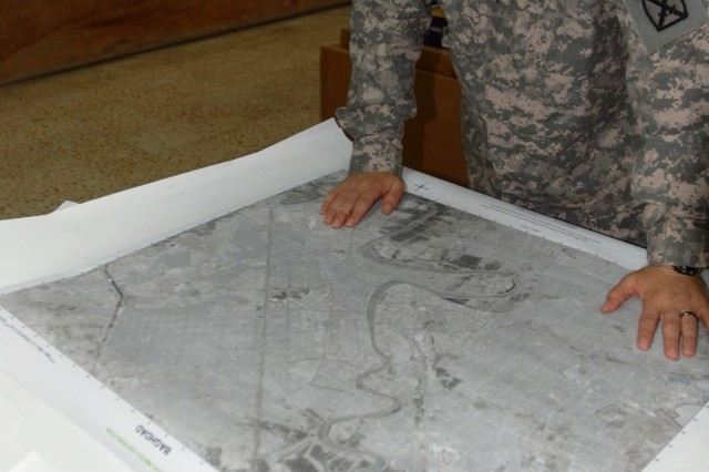 Warrant Officer 1 Mike Baber, MND-C geospatial information and services officer-in-charge, surveys a map of Baghdad.