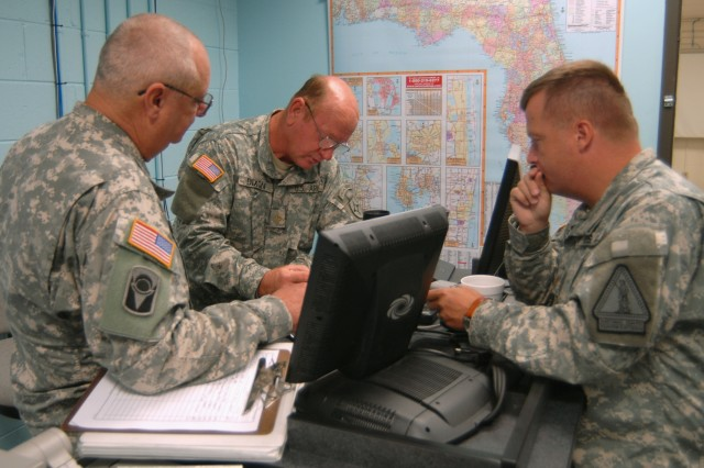 Sgt. Maj. Isham Fugate (left) and Majs. Albert Dixon and Joseph Lietz, of the Florida Army National Guard's 50th Area Support Group, plan logistics operations in preparation for Tropical Storm Fay from their unit's operations center in Homestead, Fla., Aug. 18. The Florida National Guard activated planning cells and emergency operations planners in preparation for the storm's landfall.