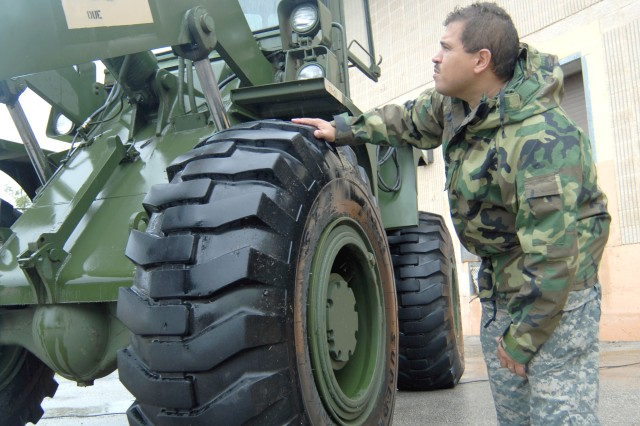 As wind and rain from Tropical Storm Fay hits south Florida, Sgt. Luis Oliva of the Florida Army National Guard's 50th Area Support Group (ASG) makes a last-minute maintenance inspection of a forklift at his unit's headquarters in Homestead, Fla., Aug. 18. In preparation for the advancing storm, a planning cell from the 50th ASG was determining possible logistics support needed to support civil authorities.