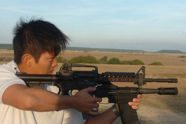Alan Kong, lead for test and evaluation on the 40M26 Modular Assault Shotgun System, demonstrates the firing technique to the Soldiers of 1st Battalion, 82nd Field Artillery Regiment July 29. Kong, employed with Program Executive Office Soldier, will take the feedback from the Soldiers to the testing area and incorporate the new ideas into the weapons system.