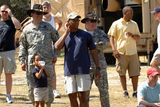 """A very simple way to shield the summer sun is to use Stetsons or baseball caps. Colonel Douglas Gabram (right in Stetson), commander of the 1st Air Cavalry Brigade, 1st Cavalry Division, Lt. Col. Charles Dalcourt (center in ball cap), commander of the 1st """"Attack"""" Battalion, 227th Aviation Regiment, 1st ACB, and Command Sgt. Maj. Glen Vela (left in Stetson), the senior noncommissioned officer for 1st ACB, watch First Attack Soldiers during their organizational day at Belton Lake Outdoor Recreational Area, Fort Hood, Texas, Aug. 14."""