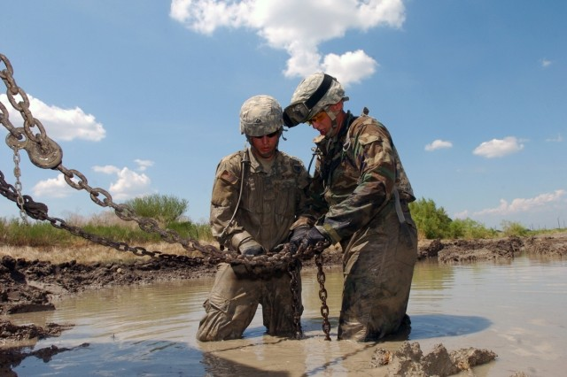Pfc. Justin Coley (left) and Spc. Joshua Boal, assigned to the Service and Recovery Shop, Company B, 15th Brigade Support Battalion, 2nd Brigade Combat Team, 1st Cavalry Division, connect chains to a stuck vehicle during recovery training Aug. 14.
