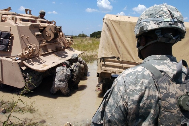 Chief Warrant Officer 2 Andre Dart, an Allied Trades technician in the Service and Recovery Shop, Company B, 15th Brigade Support Battalion, 2nd Brigade Combat Team, 1st Cavalry Division of Brunswich, Ga., watches an M88A2 Hercules Recovery Vehicle driver as he pulls a vehicle out of a deep puddle of mud during recovery training Aug. 14.