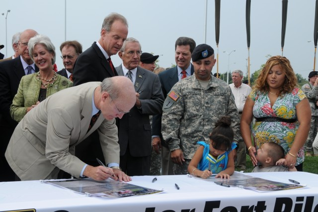"Secretary of the Army Pete Geren and the daughter of Staff Sgt. Jose and Elizabeth Vera sign their names to Greater Fort Riley Community covenants during the Army Community Covenant ceremony Aug. 20 at Fort Riley while her parents and her brother look on. <br> <br> <a href=""http://www.army.mil/-news/2008/08/20/11787-towns-show-support-for-soldiers/index.html"" target=""_blank"">See coverage of Army Community Covenant signing at Fort Sill</a> <br> <br> <a href=""http://www.army.mil/-news/2008/08/21/11794-secretary-of-the-army-tours-leonard-wood-signs-the-acc/index.html"" target=""_blank"">See coverage of Army Community Covenant signing at Fort Leonard Wood</a>"