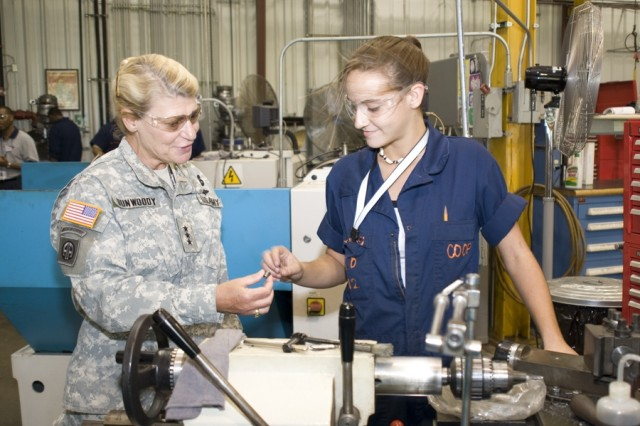 Casey Gurley, a precision machinist at the Anniston Army Depot Career Academy, explains the threading procedures used on a component for the M1A1 vehicle to Lt. Gen. (P) Ann Dunwoody.