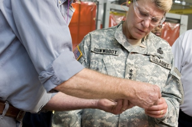 In the Anniston Army Depot machine shop, Chris Downing, welding technician, shows Lt. Gen. (P) Ann Dunwoody, AMC deputy commanding general, the different plates used for welding certification.