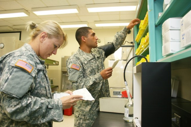 Pharmacy specialist student Pfc. Elena Teyer reads a drug information sheet while student Pvt. Roberto Valencia reaches for some meds Monday in the sterile preparation room at the Army Medical Department Center and School. After graduation, pharmacy specialists are assigned to large medical centers, smaller Troop Medical Clinics, Combat Support Hospitals, medical battalions and Brigade Combat Team medical activities.