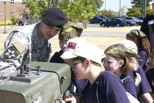 Sgt. Matthew W. Hammer, B Company, 5th Battalion, 5th Air Defense Artillery, helps show how to properly operate the Avenger Air Defense System, which is mounted atop a Humvee.
