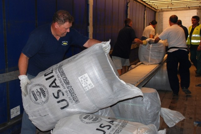 An Italian employee of the 3rd Battalion of the 405th Army Field Support Brigade helps load an 18-wheeler full of USAID wool blankets destined for Georgia as part of a USAID humanitarian assistance relief effort.   The office of U.S. Foreign Disaster Assistance sent aid to the Philippines and Myanmar earlier this summer.