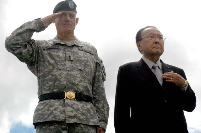 Senator Daniel K. Inouye and Maj. Gen. Robert L. Caslen Jr., commanding general, 25th Infantry Division, honor the playing of the National Anthem during a Medal of Honor flag presentation ceremony held at Schofield Barracks' Sills Field, Aug. 20.