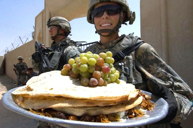 "Sgt. Alyson Brown displays a platter of food provided to U.S. soldiers at the end of government-led meetings in Wajihiyah, Iraq, Aug. 16.  <br> <br> Aug. 26 is Women's Equality Day. For more on Women in the Army please visit <a href=""http://www.army.mil/women/"">Women in the U.S. Army website</a>"