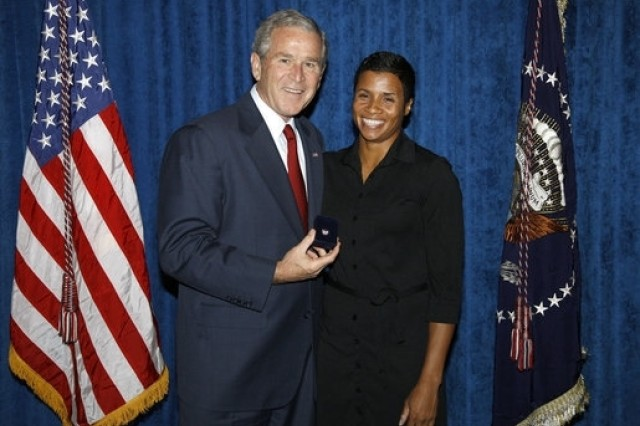 President George W. Bush stands with Keela Carr, a 35-year-old fitness and athletic trainer, shortly after his arrival Aug. 20, in Orlando, Fla. Ms. Carr was recognized by the U.S. Army's Freedom Team Salute Program and named its 500th Volunteer Ambassador in recognition of her 2008 2,700-mile, trans-America Journey of a Thousand Thanks to honor and thank all soldiers and veterans.