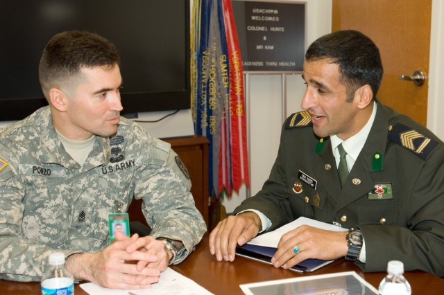 Afghan medical CSM and CHPPM Sgt. Maj. Osvaldo discuss preventive medicine measures.