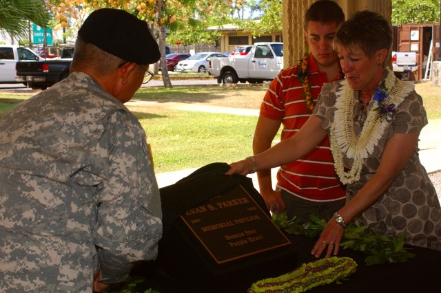 FORT SHAFTER FLATS, Hawaii - (From left to right) Maj. Gen. Vern Miyagi, mobilization assistant to the commander, U.S. Pacific Command; Caleb Foster, brother; and Anita Foster-Dixon, mother, unveil a plaque for the late Sgt. Evan Parker during a pavilion dedication ceremony, Aug. 18. Parker was an Army Reserve Soldier with the 9th Mission Support Command who was killed while supporting Operation Iraqi Freedom in 2005.