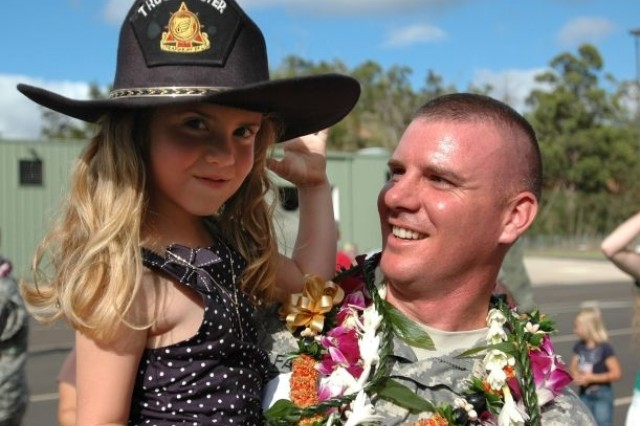 WHEELER ARMY AIRFIELD, Hawaii - Jacquelyn Farmer, daughter of Sgt. 1st Class Robert Farmer, 25th Transportation Company, looks into the camera while being held by her father, following his unit's welcome home ceremony at Wheeler Army Airfield, Aug.