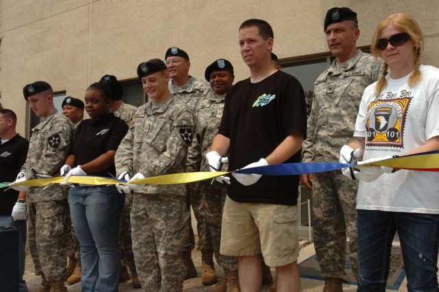 Col. Joseph A. Bassani, (second from right), commander of 2nd CAB, looks on as Soldiers and Family members cut a ribbon signifying the grand opening of the newly refurbished CAC at Camp Eagle July 18. The new building, which was once used as a component repair facility, was renovated to improve the quality of life for those living at the military base.
