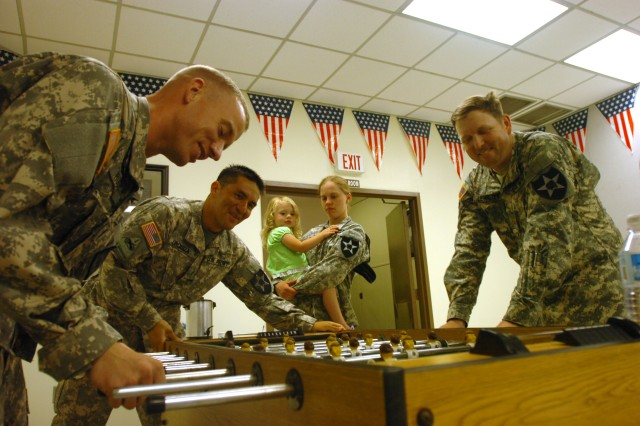 Aspen Zesiger (middle) watches as Soldiers play a game of foosball after the grand opening of the new Community Activities Center at Camp Eagle July 18.