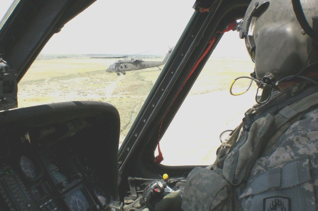 JOINT BASE BALAD, Iraq - A UH-60 Black Hawk pilot, assigned to 5th Battalion, 158th Aviation Regiment's Task Force Ready, scans the terrain over Iraq during a mission. TF Ready pilots have flown more than 30,000 hours during a 15 month deployment in support of Operation Iraqi Freedom. The task force included Soldiers and aircraft from four battalions who came together in theater to fly multiple mission sets for Task Force XII and Multi-National Corps - Iraq.