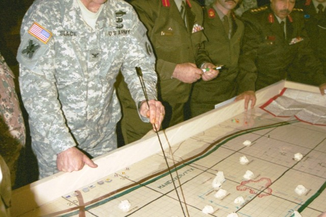 """New York Army National Guard Col. Geoffrey Slack, the operations officer of the 42nd Infantry Division, reviews the scheme of maneuver for a joint/combined exercise over a """"sand table."""" Sand tables were one of the earliest forms of military simulation, beginning with the roman legions' use of them in the first century A.D."""