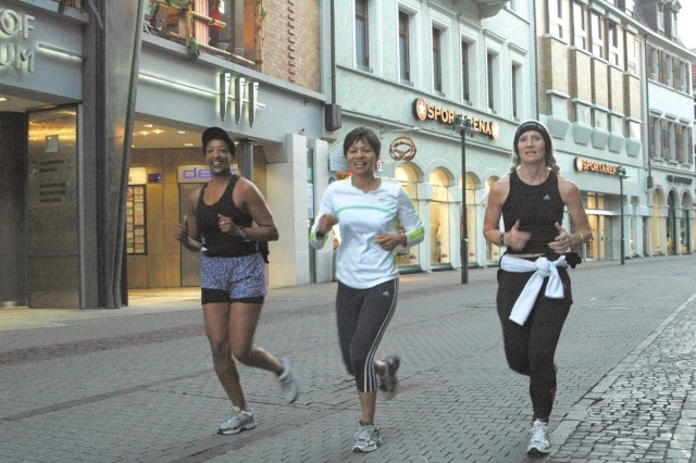 Gloria Steed, center, runs with Steffani Paoletti and Yodit Tadesse on Heidelberg's Hauptstrasse Tuesday morning. Steed is training for the Athens Classic Marathon in November while battling cancer.