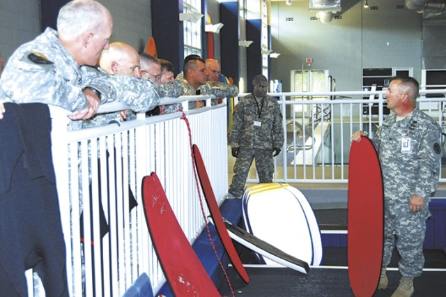 Col. David Bitterman, Brooke Army Medical Center deputy commander of administration, stands inside the Flowrider Aug. 20 at the Center for the Intrepid and explains the different types of boogie boards Warriors in Transition use depending on their injuries. Attendees from the Initial Entry Training Forum visited the facility to learn about the work that is being performed at Fort Sam Houston.""