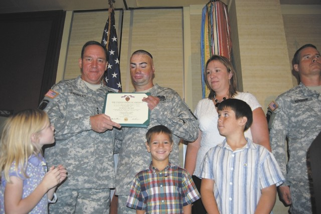 Lt. Gen. Benjamin Freakley, commanding general of the Army Accessions Command, and Staff Sgt. Shiloh Harris hold the Purple Heart medal award citation Harris received Aug. 19 at the Marriott Riverwalk Hotel in San Antonio. Harris was injured during an improvised explosive device in Feb. 2007, in Iraq. The Harris family attended the award ceremony.