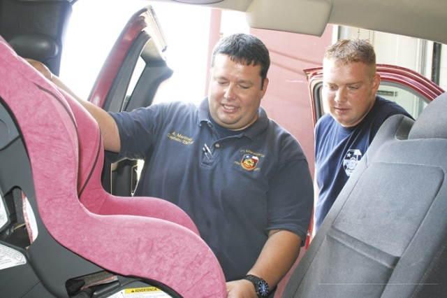 Capt. Adam Martinez, Fort Sam Houston Fire and Emergency Services, inspects a car seat for Firefighter Daniel Cobb at the fire department. Firefighters not only provide emergency services for the post, but help the community through fire-prevention programs and car-seat inspections.