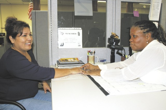 "Bessie Scott, site and security manager, ID Card Section, takes a fingerprint reading from Patricia Arzola so she can issue Arzola a new ID card Aug. 25 at the In and Out Processing Center. ""I love customer service,"" Scott said. ""I love to work with Soldiers and all of my customers."""