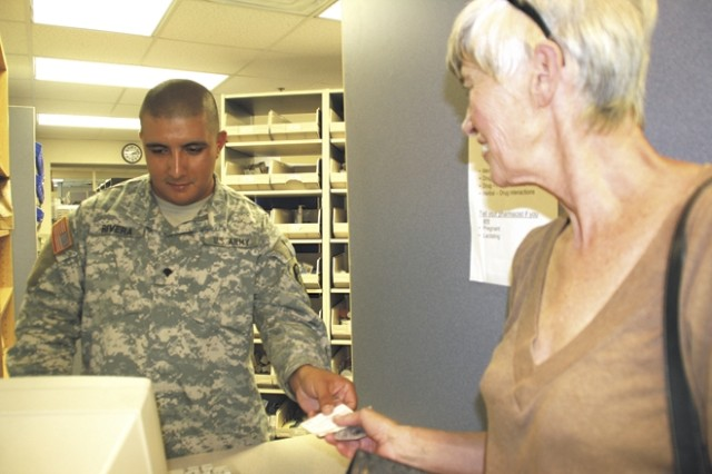 "Spc. Anastacio Rivera fills a prescription Aug. 25 for Susan JuVette at the Satellite Pharmacy here. Rivera, a pharmacy technician, said he enjoys helping patients get the prescriptions they need. ""I really enjoy helping retirees. I feel like I'm returning a favor,"" he said."