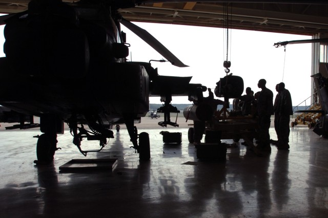 "Crew chiefs from 1st ""Attack"" Battalion, 227th Aviation Regiment, 1st Air Cavalry Brigade, 1st Cavalry Division, silhouetted by the harsh light of the sun, work on a hoisted AH-64D Apache attack helicopter engine during their daily maintenance operations at Robert Gray Army Air Field, Fort Hood, Texas, Aug. 26."