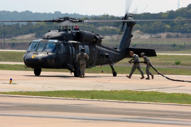 "Soldiers from 4th ""Guns"" Battalion, 227th Aviation Regiment, 1st Air Cavalry Brigade, 1st Cavalry Division, refuel a UH-60 Black Hawk from 3rd ""Spearhead"" Battalion, 227th Aviation Regiment, 1st ACB, during flight operations at Robert Gray Army Air Field, Fort Hood, Texas, Aug. 26."