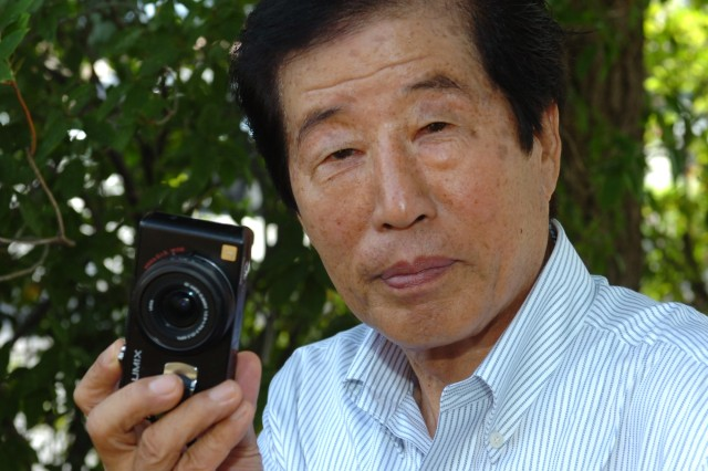 Yu, Hu Son poses with his personal camera that he has used to capture images of the Soldiers and Airmen serving in the Warrior Division over the past 11 years. He is celebrating 50 years of service to the U.S. Army.