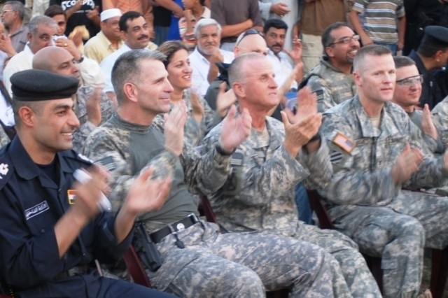Maj. Gen. Michael Oates, Multi-National Division - Center and 10th Mountain Division commander, and Col. Thomas James, 4th Brigade Combat Team, 3rd Infantry Division commander, applaud a song played by the 10th Mtn. Div. Band and the Seddah School District Band Aug. 23 in Seddah, Iraq.