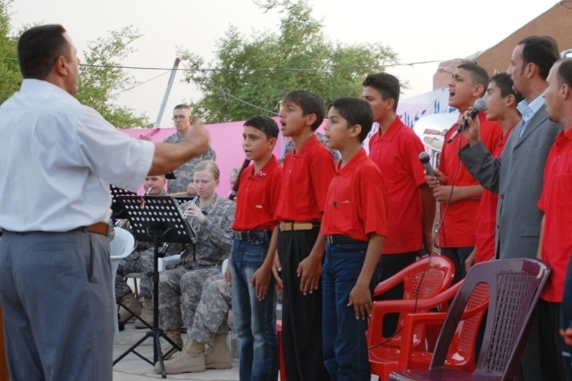 The Seddah School District Band, accompanied by the 10th Mtn. Div. Band, sings the Iraqi National Anthem during a concert in Seddah Aug. 23.
