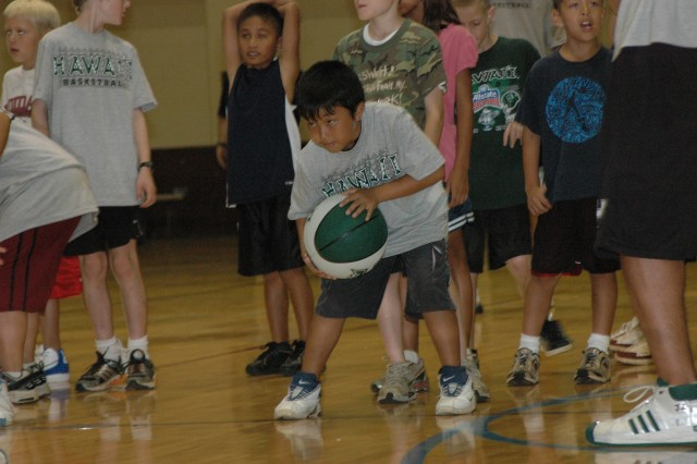 SCHOFIELD BARRACKS, Hawaii - Nicholas Furusho gets ready to run in the dribbling race at the University of Hawaii's Men's Basketball Team clinic at Martinez Gym, Aug. 19. Teammates and coaches experienced a taste of Army life during the day and shared their basketball knowledge at the gym in the afternoon, Aug. 18-22.