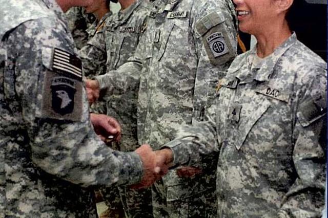 Carol David, budget analyst, 25th Infantry Division, greets Gen. David Petraeus, commander, Multinational Forces-Iraq, during a recent deployment.